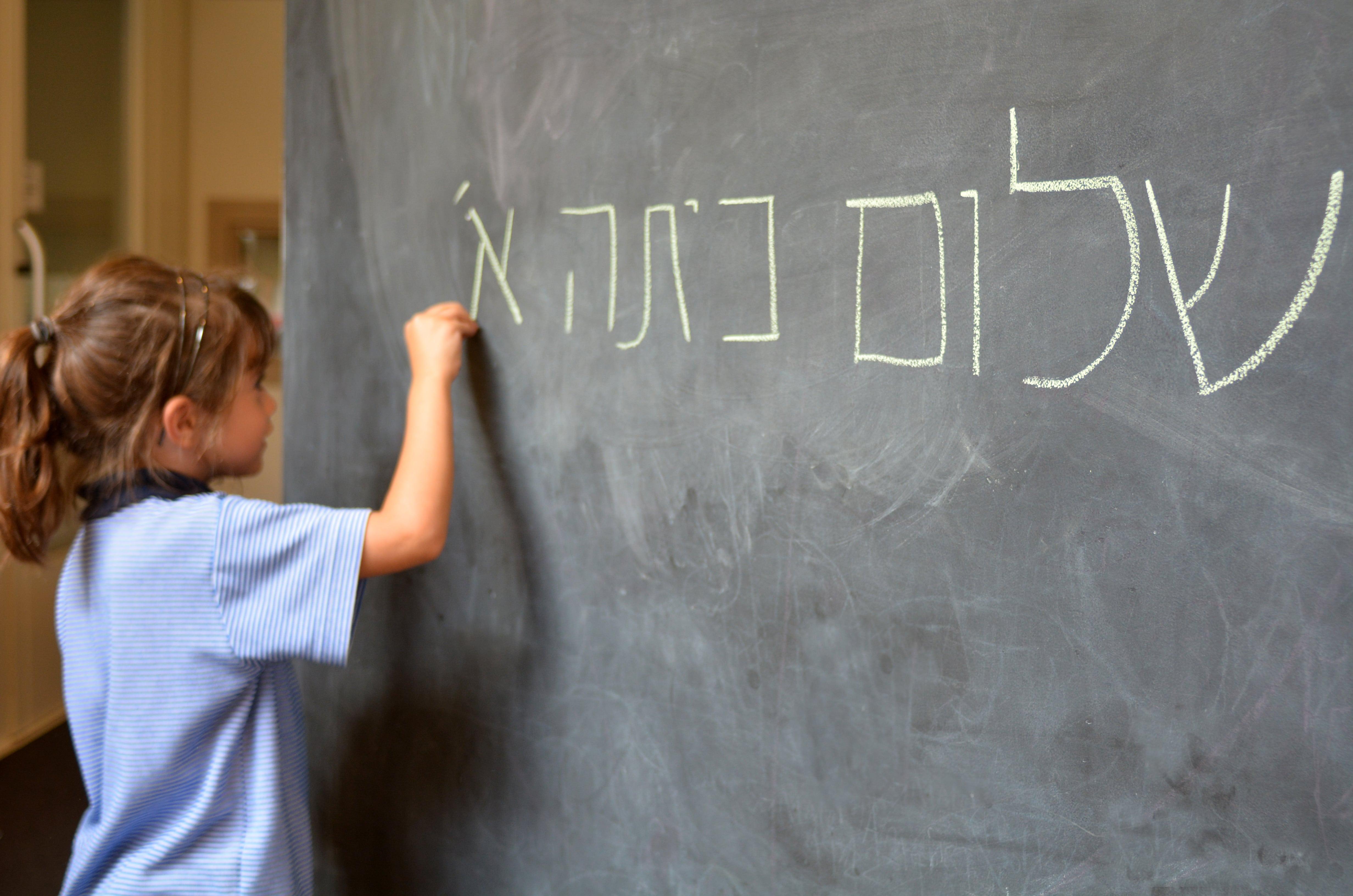 Photo d'une petite fille blonde tenant un bout de craie pour écrire en hébreux sur un tableau noire